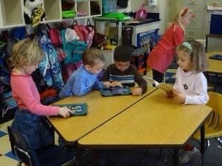 Young children engaged with an iPad